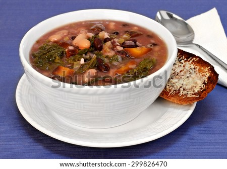 A white bowl of kale, beans and vegetable soup with a side of cheesy bread.  Close up.