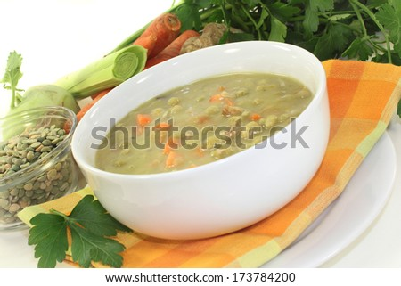 a white bowl of pea soup and parsley