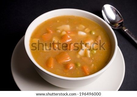 A white bowl with an orange soup and a spoon. - stock photo