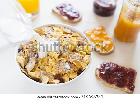 A white bowl with cornflakes and a bottle pouring milk on a white wood table. There are three toasts with jars of homemade jam and raisins. - stock photo