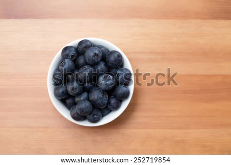 A white bowl with ripe blueberries on a table,  shallow dof - stock photo