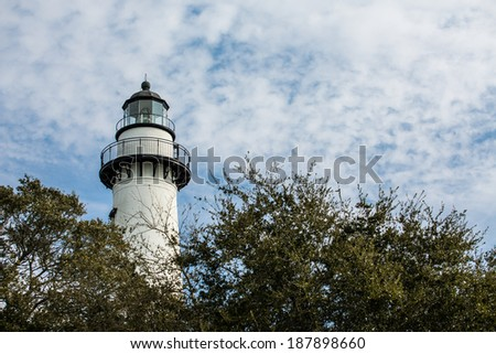 A white brick lighthouse rising out of green foliage under clear blue skies