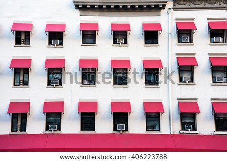 A white building with repetitive pink window shades in Manhattan. - stock photo