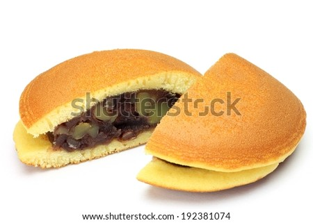 A white cake cut in half with food in the middle. - stock photo