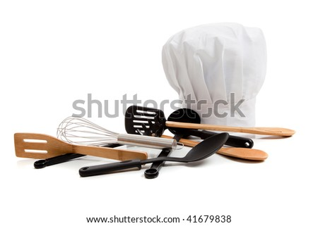 A white chef's toque with various cooking utensils including a wisk, wooden spoons, spatulas on a white background - stock photo