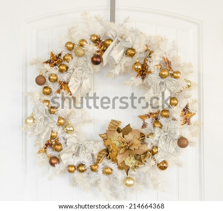 A white Christmas wreath with gold ornaments on a white door - stock photo