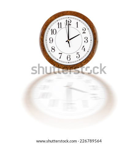 A white clock face in brown wooden frame showing two o'clock over white background with blurry reflection