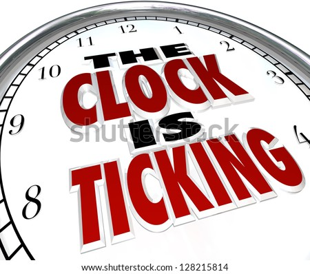 A white clock with the words The Clock is Ticking to symbolize an impending deadline or end to an event or period - stock photo