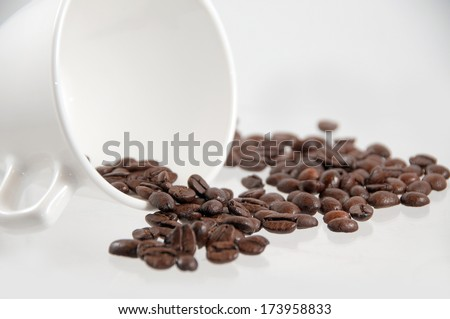 A white coffee cup fallen over with coffee beans spilling out