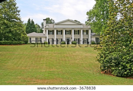 A white columned mansion on a grass hill