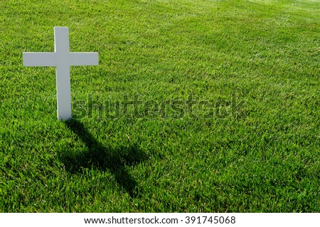 A white cross on a grave, with green grass in the back.  - stock photo