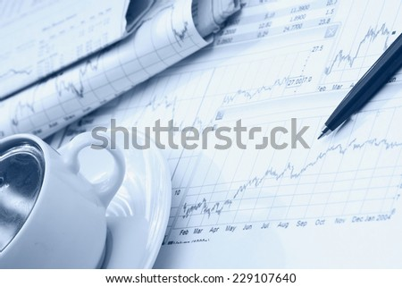 A white cup of cappuccino and a pen on papers - stock photo