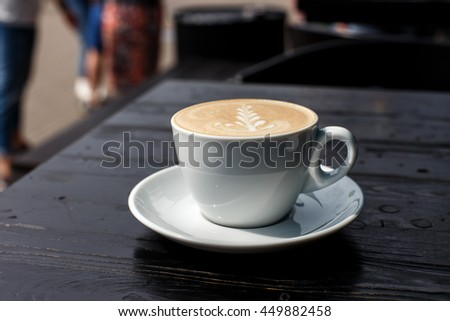 A white cup of cappuccino on the dark wooden table