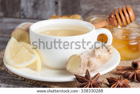 A white cup of green natural tea with ginger, lemon and honey on wooden rustic background. Healthy drink. Hot winter beverage concept. - stock photo
