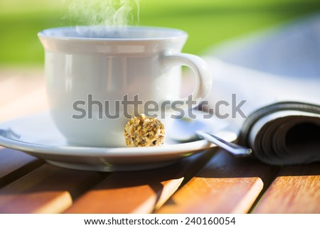 a white cup of hot coffee on wood table with newspaper and area for your text - stock photo