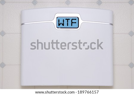 A white digital bathroom scale displaying the text message WTF.