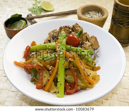 A white dish full of stir-fry mixed vegetables (red and green pepper, carrots, potatoes and asparagus) and tofu cubes, surrounded by a bamboo cup, chopsticks, lime and black and white sesame seeds. - stock photo