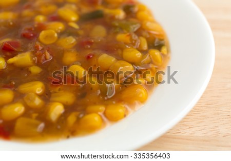 A white dish with corn relish on a wood table top illuminated with natural light.