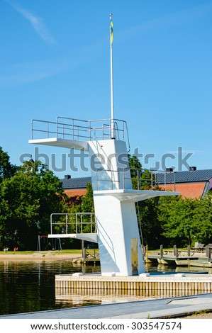 A white diving board or tower against a clear blue sky. Reflections are seen underneath. No person visible. - stock photo