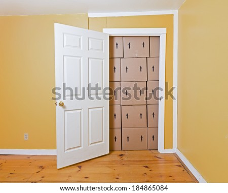A white door opens in a yellow room to reveal a room full of brown cardboard boxes. - stock photo