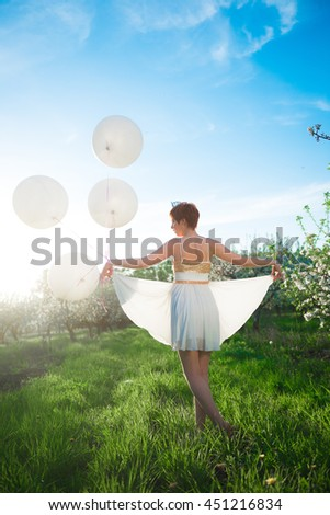 A white dressed girl walking in a green garden with huge white air balloons, her back to us