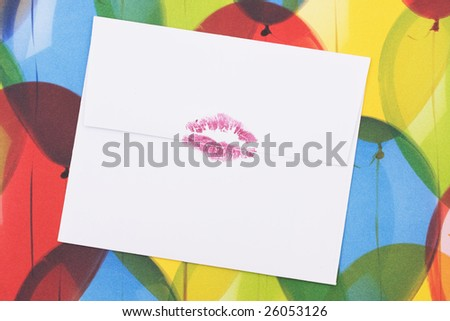 A white envelope with a red lipstick kiss sealing it sitting on a colourful balloon background, sealed with a kiss - stock photo