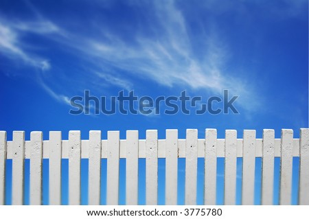 A white fence and blue sky. - stock photo