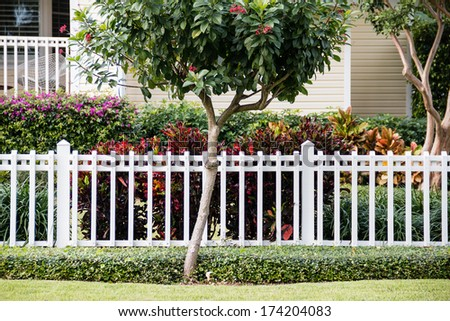 A white fence in front of a cozy and representative home with a very well-groomed green lawn