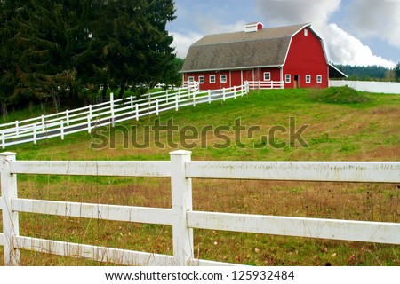 A white fence leading up to a big red barn - stock photo