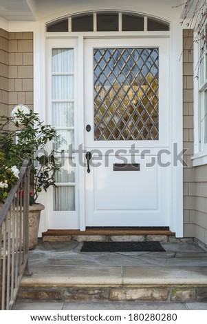 A white front door to a beige home, with an intricate, diagonal paned window. Also seen is a stone porch and stairs, railing, and a plant.  - stock photo