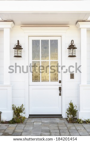 A white front door to a classic white family home in daytime. Door features intricate etched detail. Also seen is columns, a stone porch, and light fixtures.