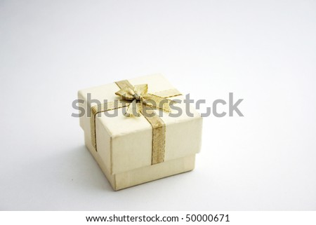 A white gift box or jewelry box with gold ribbon bow-knot.
