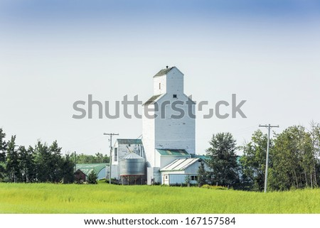 A white grain elevator standing tall on the prairies