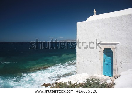 A white Greek ortodox churche in Mykonos with blue sea on the background - stock photo