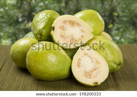 A white guava cut in a alf in over some entire white guavas over a green surface on a plantation background.