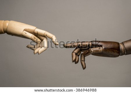 A white hand and black hand behind their fingers to touch. On grey background. Mimic of Creation of Adam by Michelangelo. - stock photo