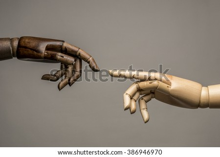 A white hand and black hand behind their fingers to touch. On grey background. Parody Michelangelo. - stock photo