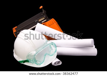 A white hard hat with safety goggles, rolled up blueprints, and an orange nail gun.  Isolated on a black background. - stock photo