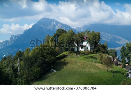 a white house on top of a hill at Piani d'Erna (part of the Alps) near Lake Como in Italy - stock photo