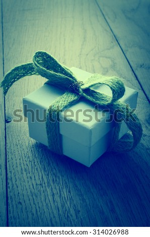 A white, lidded square gift box on an old oak planked table, tied to a bow with a soft green wooly fabric ribbon, and wrapped with a shiny gold thread.  Cross processed for retro or vintage effect. - stock photo