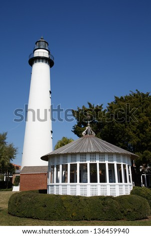 A white lighthouse under clear blue skies with a white gazebo