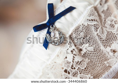 A white linen garter with a blue bow - stock photo