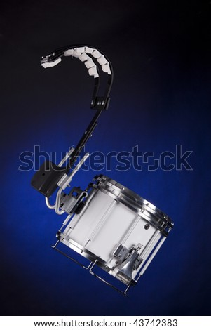 A white marching field drum and carrier isolated against a spotlight blue background.