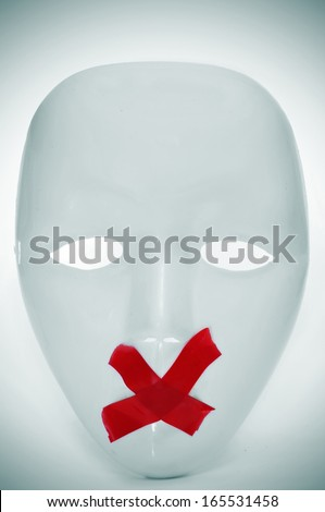 a white mask with its mouth shut with red tape, depicting the lack of freedom of speech - stock photo