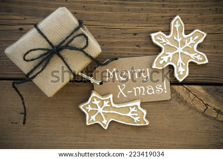 A White Merry X-mas on a brown Label with Christmas Decoration on Wood