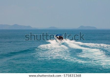 A white motor boat speeding away across a blue bay
