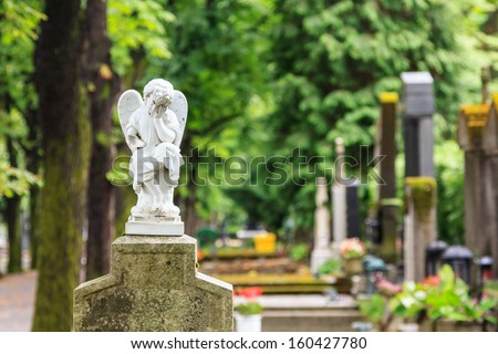A white mourning porcelain angel on a cross in Mirogoj cemetery, Zagreb, Croatia - stock photo