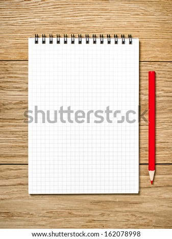 A white note book with lots of room for your text or image and a regular pencil on a wooden desk
