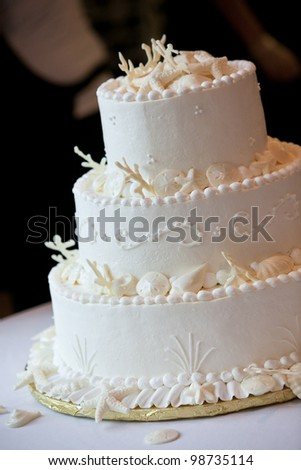 a white ocean themed wedding cake with miniature seashell design and details - stock photo