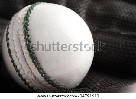 A white one day or twenty-20 match cricket ball in a wicket keeping glove.